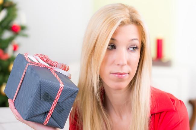 クリスマスプレゼントを手に浮かない顔をしている女性