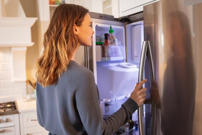 キッチンで冷蔵庫を開けている女性