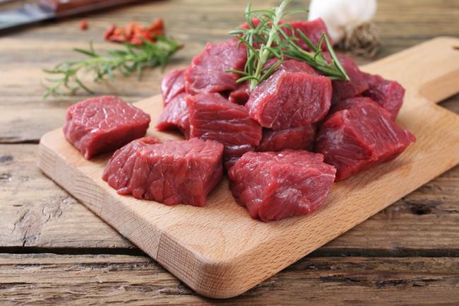 まな板の上に置かれた生肉とハーブ