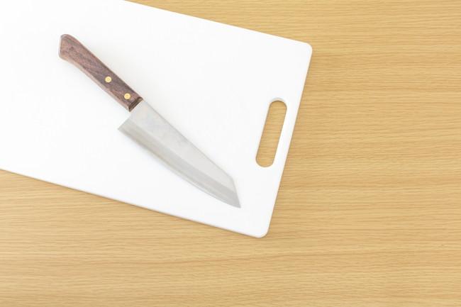 台の上に置かれた白いまな板と包丁