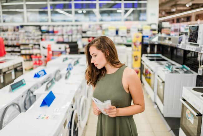 家電量販店で乾燥機をよく見ながら選んでいる女性