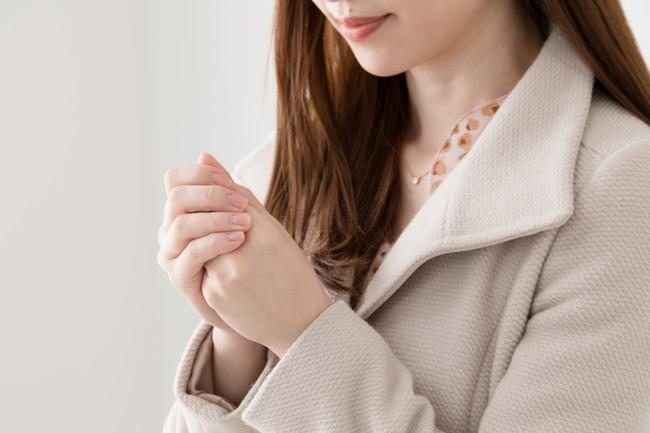コートを着て手を温める女性
