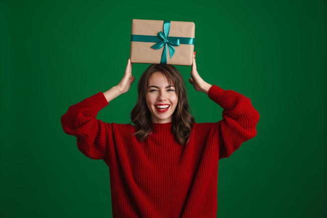 クリスマスギフトボックスを頭の上に乗せ笑顔の女性