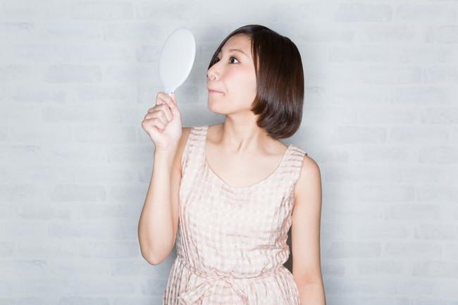 鏡を見てムダ毛をチェックする女性