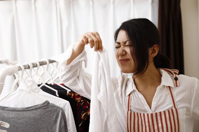 洗濯物をつまんで臭いと感じている主婦