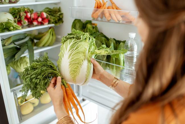 冷蔵庫を開けて野菜を取り出している女性