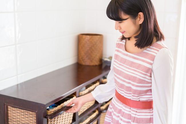 整理整頓された棚と片づけをしている女性