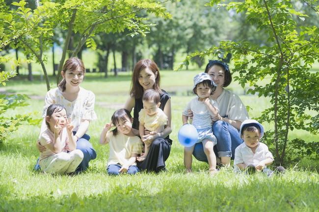 緑あふれる公園で遊ぶ親子の集合写真
