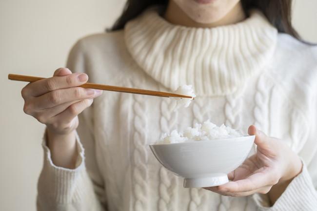 茶碗に盛られた白米と箸を持つ女性の手元