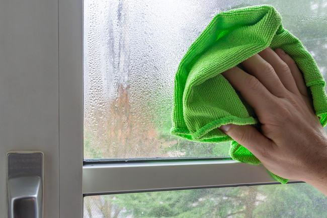 窓の結露をクロスで拭きとっているところ