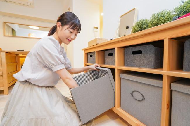 収納ボックスで棚の片付けをする女性