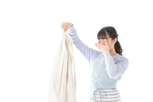 洗濯物をつま臭い表情をしている女性