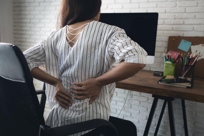 パソコンをしながら腰痛を気にしている女性