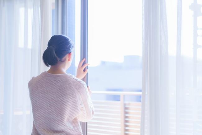 カーテンと窓を開けて換気している女性