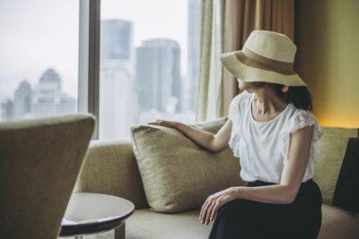 ソファーに座って窓の外を眺める女性