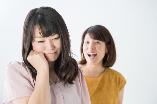 友人に話しかけられているが友人関係に悩んでいる様子の女性