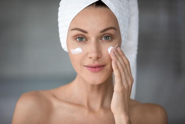 ニベアクリームを頬に塗る女性