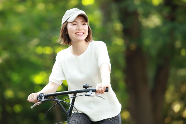 帽子をかぶって自転車に乗る女性
