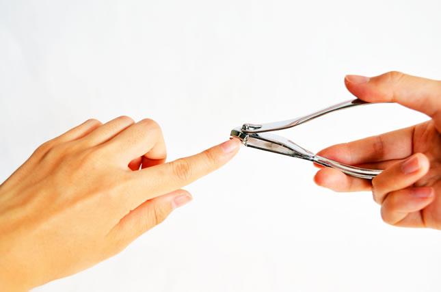 爪切りで爪を切る女性