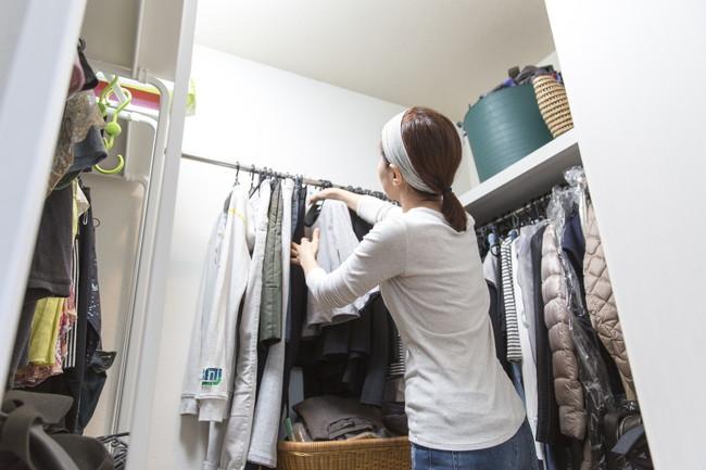 クローゼットの中にコートをかけている女性