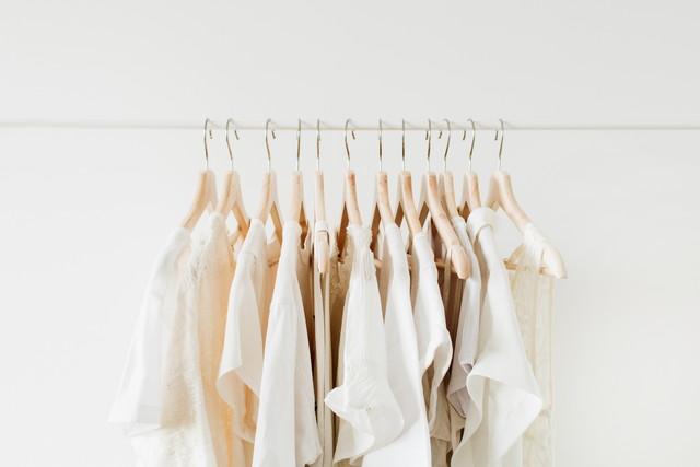 木製のハンガーにかけられた白系の服