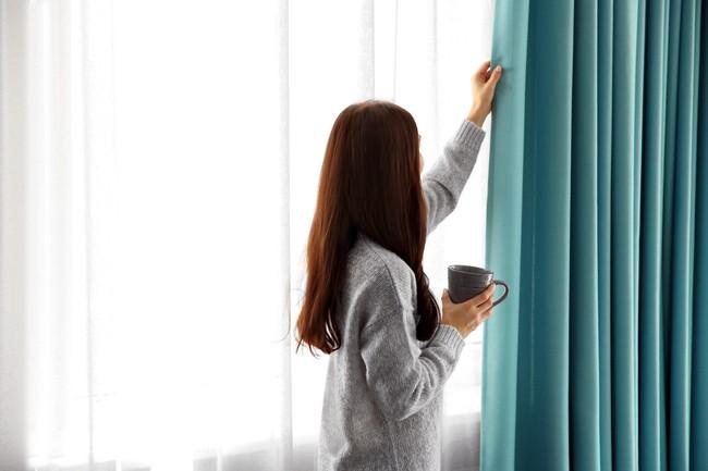 コーヒーカップを片手にドレープカーテンをあける女性