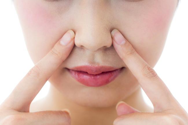 小鼻を人さし指で押さえている女性の顔