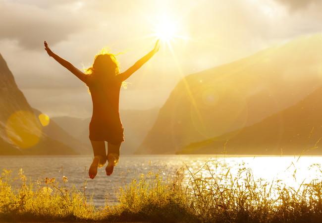 自然の中で高いところから飛び降りて着地しようとしている女性