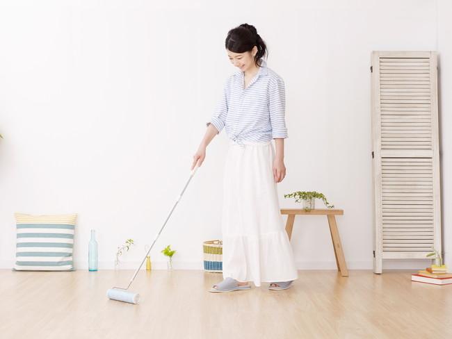 フローリングをコロコロで掃除をしている女性
