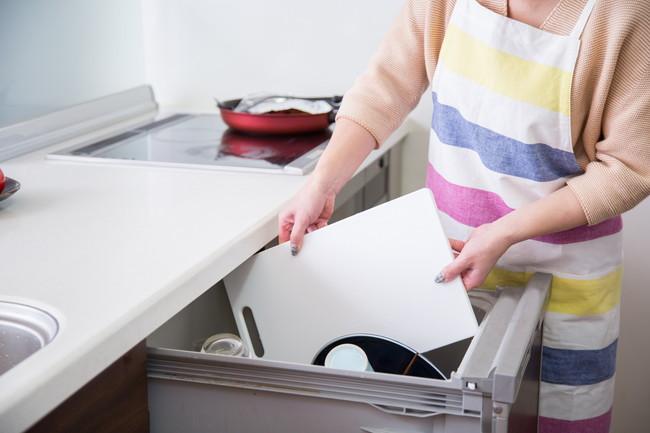 食洗機に白いまな板を入れる女性