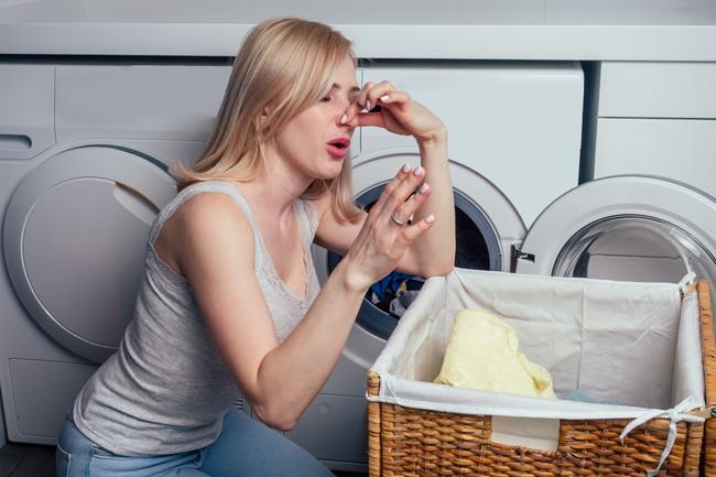 洗濯カゴの前で鼻をつまみ臭い顔をしている女性