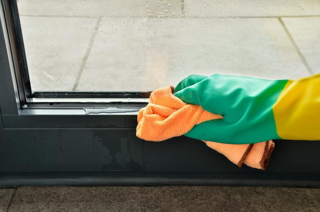結露した窓のサッシをクロスで拭いているところ