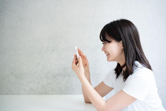 楽しそうにスマートフォンを見ている女性