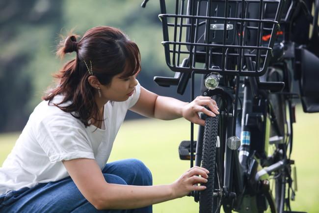 故障した自転車を直そうとしている女性