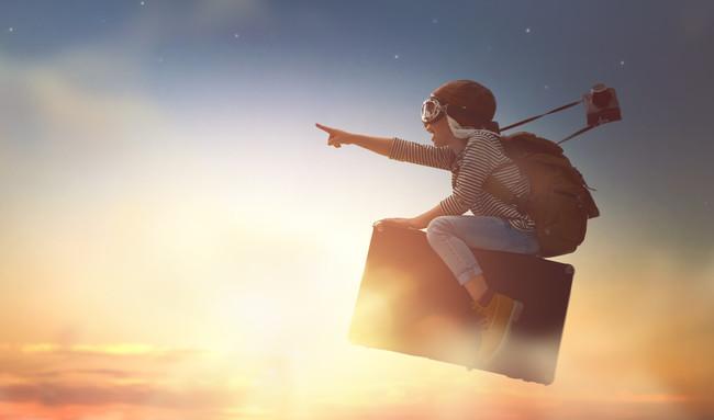 スーツケースにまたがって空を飛んでいる子供