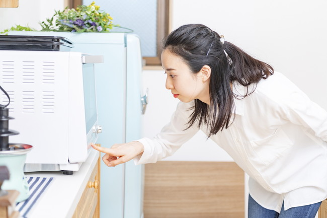 キッチンで電子レンジを操作する女性