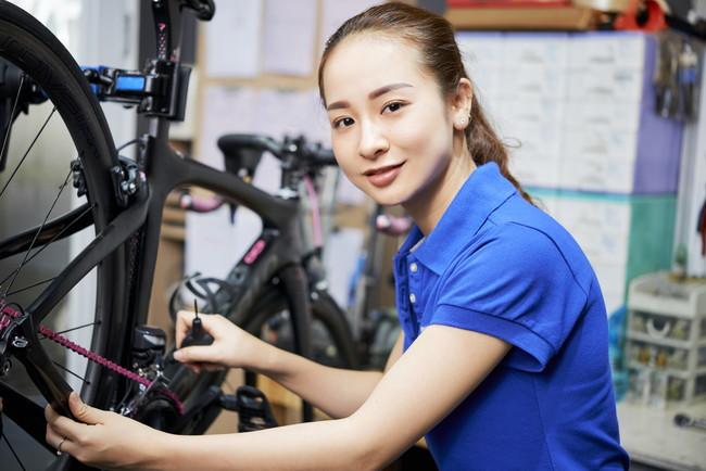 自転車を修理している女性スタッフ