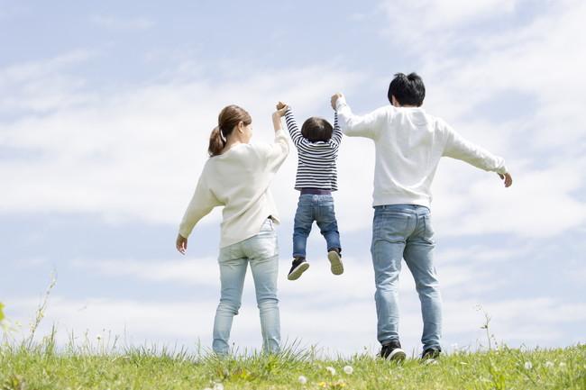 青空の下の若い家族の全身後ろ姿