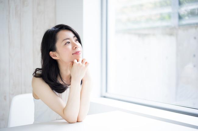 窓際で座って考え事をしている女性