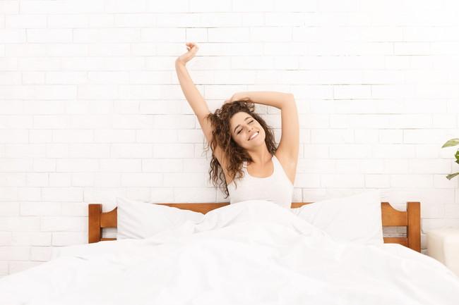 ベッドで微笑んでいる寝起きの女性