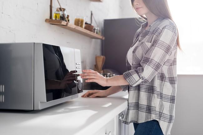キッチンで電子レンジを操作している女性