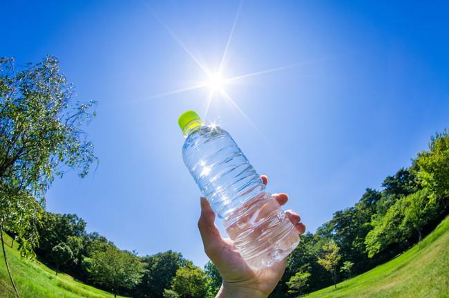 公園で青空の下ペットボトルの水を持っている