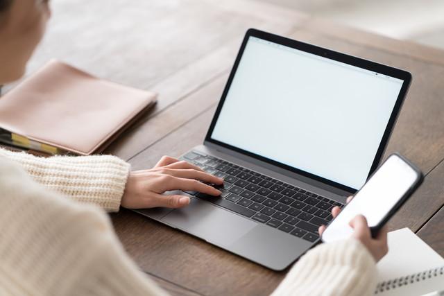スマホとパソコンを操作する白い服の人_