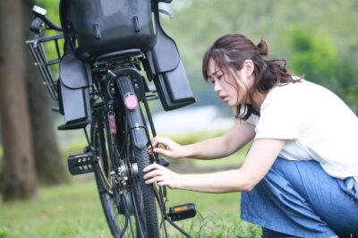 自転車が故障しているか確認している女性