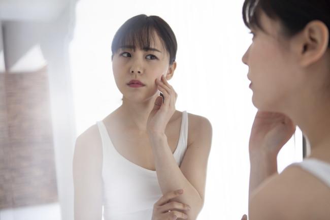 自分の肌を確認する若い女性