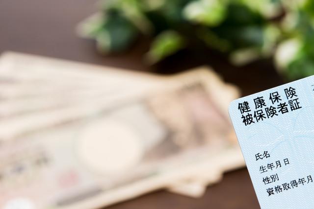青い保険証の奥に複数の一万円札