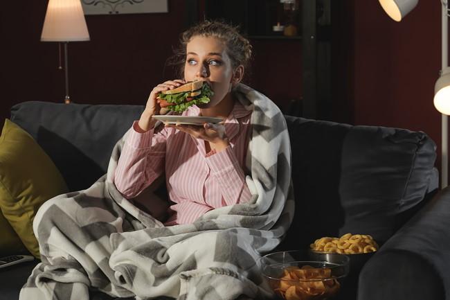 パジャマを着てソファでサンドイッチを食べている女性
