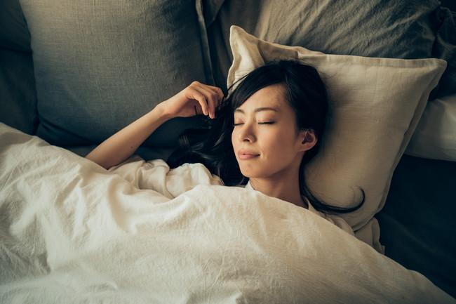 布団の中で睡眠中の女性