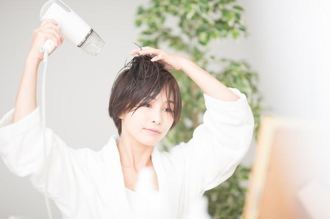 入浴後にドライヤーで髪を乾かしている女性