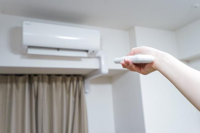 リモコンを使いエアコンを操作しているところ
